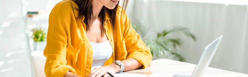 Kvinna skriver på affärsplan till eget företag