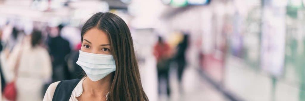 Person med munskydd för att undvika smitta