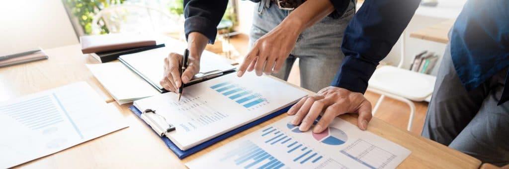 Två män vid ett bord som går igenom statistik