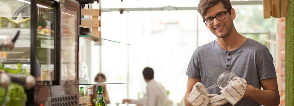 Leende man som putsar ett glas i sin restaurang