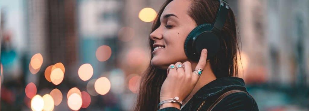Kvinna med hörlurar som lyssnar på podd