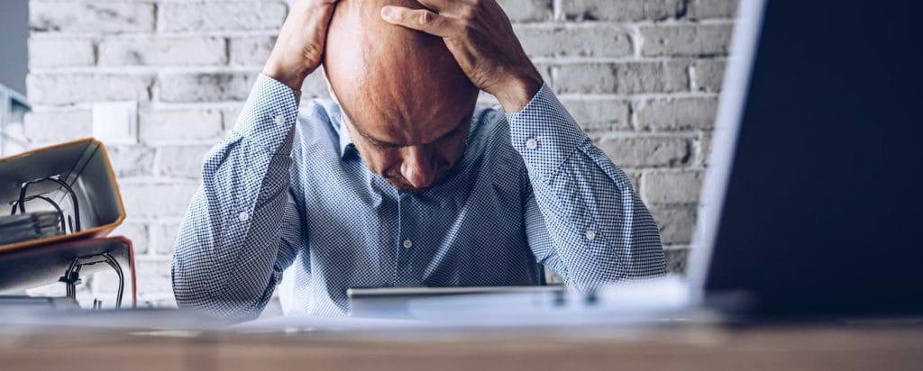 Stressad företagare med huvudet i händerna