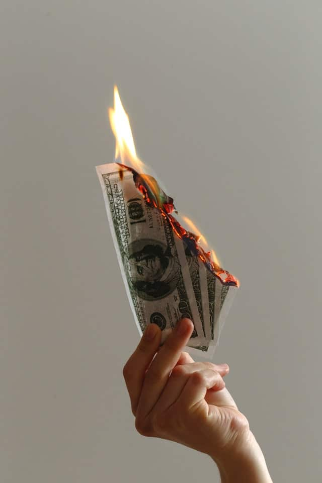 En hand som håller i brinnande dollarsedlar.