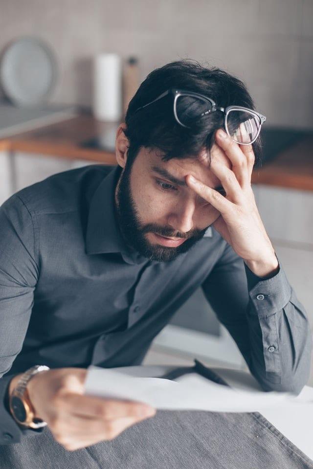En förtvivlad man som läser ett dokument.