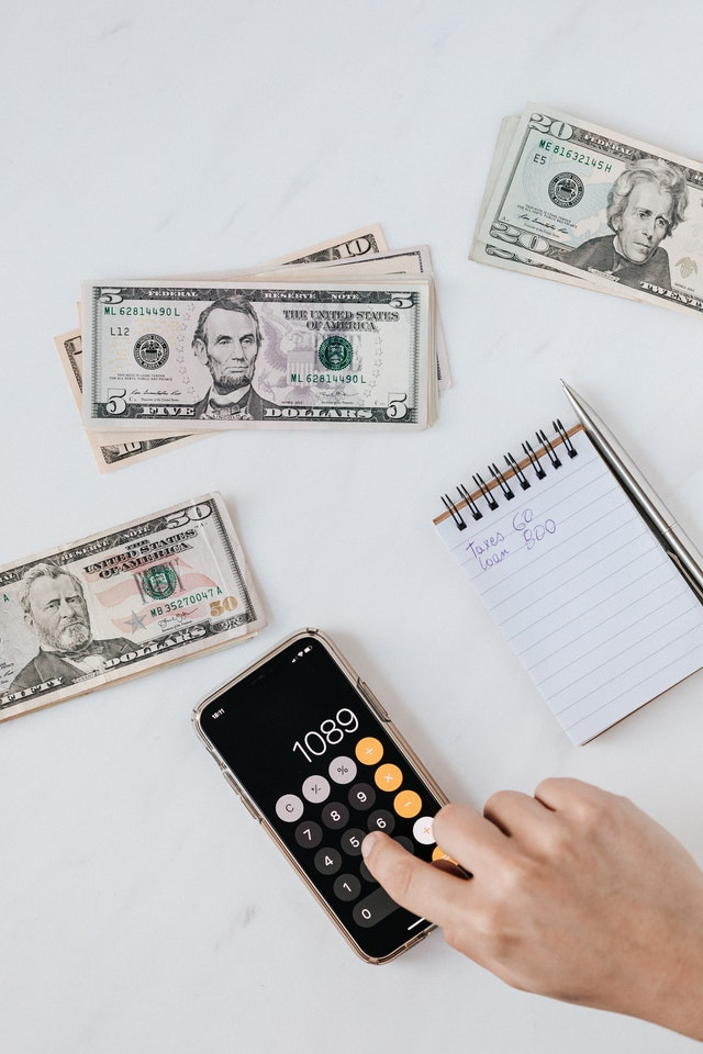 En mobiltelefon med en miniräknare samt en mängd amerikanska dollarsedlar.